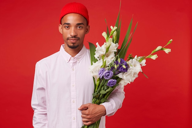 Jonge rustige afro-amerikaanse man in wit overhemd en rode hoed, boeket houdt, staat op rode achtergrond en kijkt naar de camera. Gratis Foto