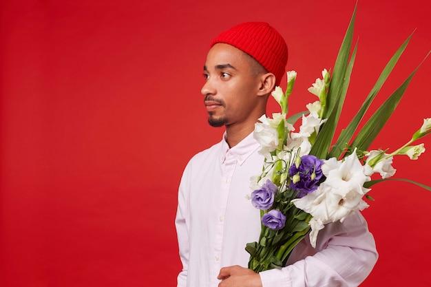 Jonge rustige afro-amerikaanse man in wit overhemd en rode hoed, kijkt weg en houdt boeket, staat op rode achtergrond. Gratis Foto