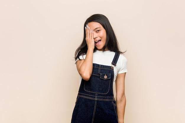 Jonge schattige chinese tiener jonge blonde vrouw die een laag draagt tegen een roze muur die pret heeft die de helft van het gezicht bedekt met palm. Premium Foto