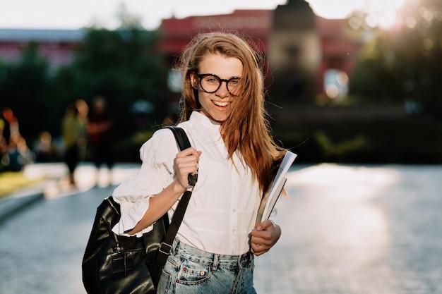 Jonge schattige stijlvolle vrouwelijke student wit overhemd en bril dragen Gratis Foto