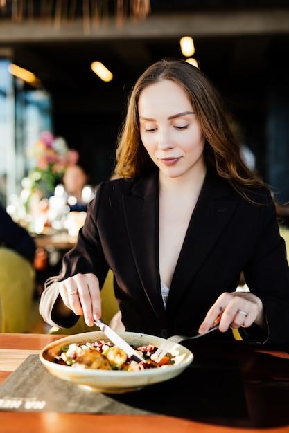 Jonge schoonheid vrouw gezond eten zittend in het prachtige interieur met groene bloemen Gratis Foto