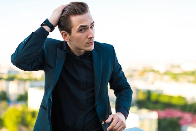 Jonge serieuze busunessman in donker pak, horloge en zwart shirt staan op het dak Premium Foto