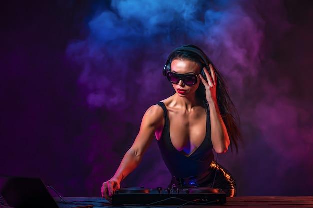 Jonge sexy dj met zonnebril die muziek speelt Premium Foto