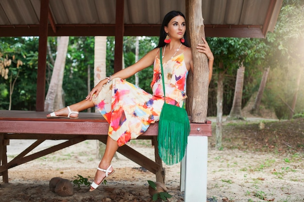 Jonge sexy mooie vrouw in kleurrijke jurk zomer hippie stijl, tropische vakantie, gebruinde benen, sandalen, groene handtas met franje, accessoires, glimlachen, gelukkig Gratis Foto
