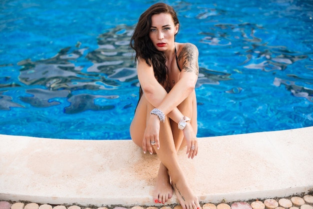 Jonge sexy vrouw dicht bij zwembad dat zwart zwemmend kostuum draagt Premium Foto