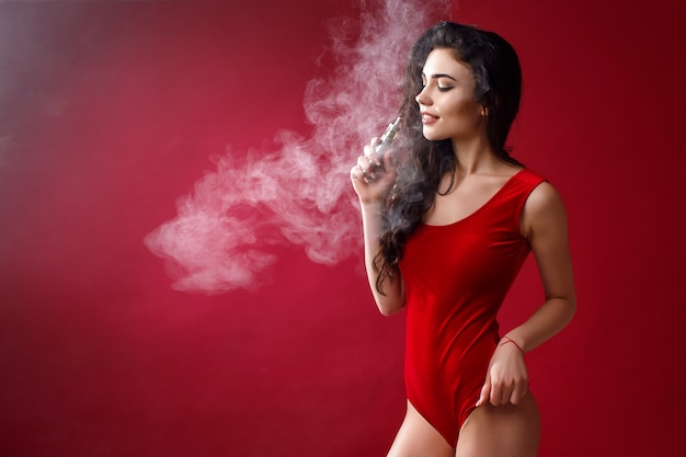 Jonge sexy vrouw is vapen. een wolk van damp. studio-opnamen. Premium Foto