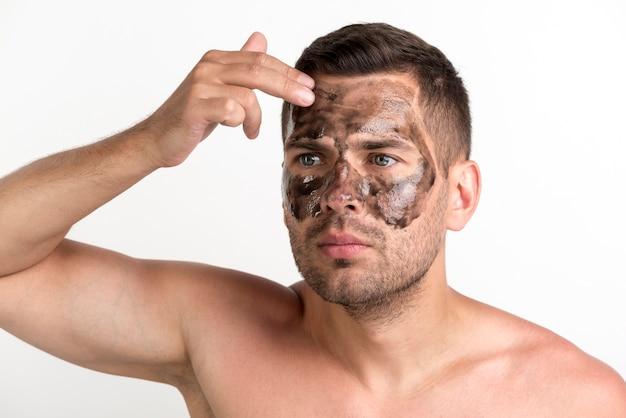 Jonge shirtless man zwart masker op gezicht toe te passen Gratis Foto