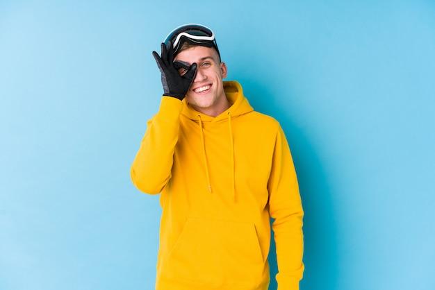 Jonge skiërmens opgewonden het houden van ok gebaar op oog. Premium Foto