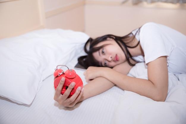 Jonge slaapvrouw en wekker in slaapkamer thuis Gratis Foto
