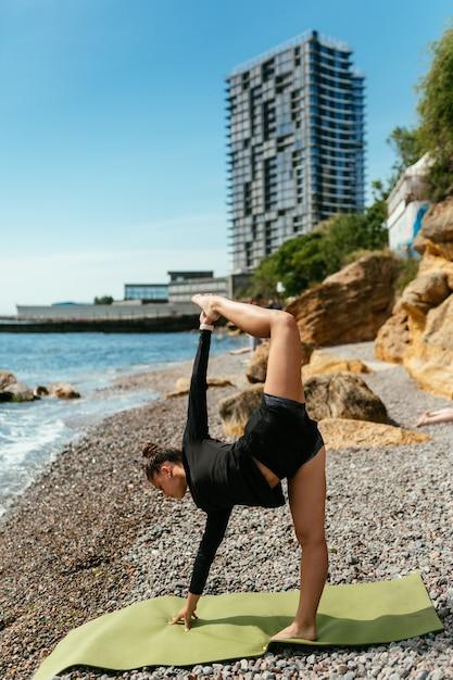 Jonge slanke vrouw die oefening voor spier op yogamat doet buitenshuis bij kiezelstrand aan zee Gratis Foto