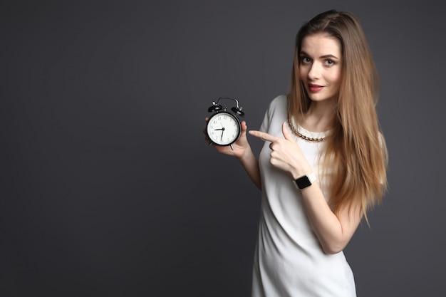 Jonge slanke vrouw die op wekker op grijze achtergrond richt Premium Foto