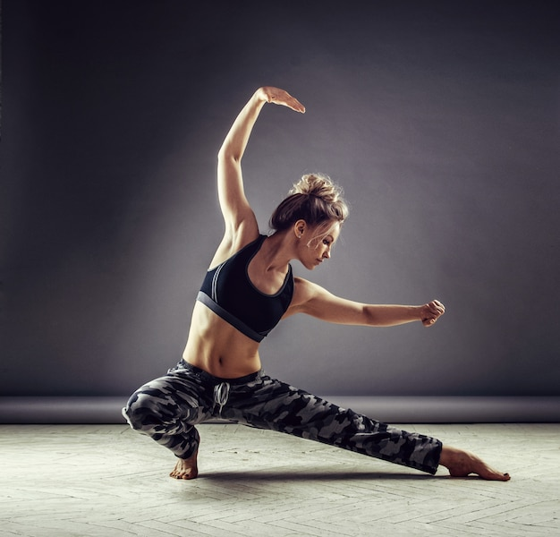 Jonge slanke vrouwendanser in sportkleding springen hoog op muur achtergrond Premium Foto