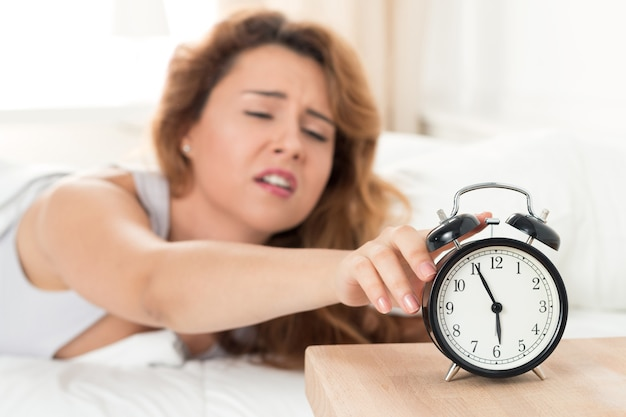 Jonge slaperige vrouw die de wekker probeert uit te schakelen Premium Foto