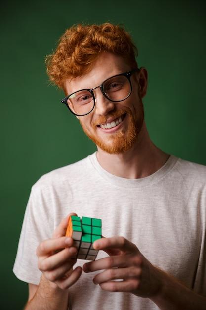 Jonge slimme readgead bebaarde man in glazen, spelen met rubic's kubus Gratis Foto