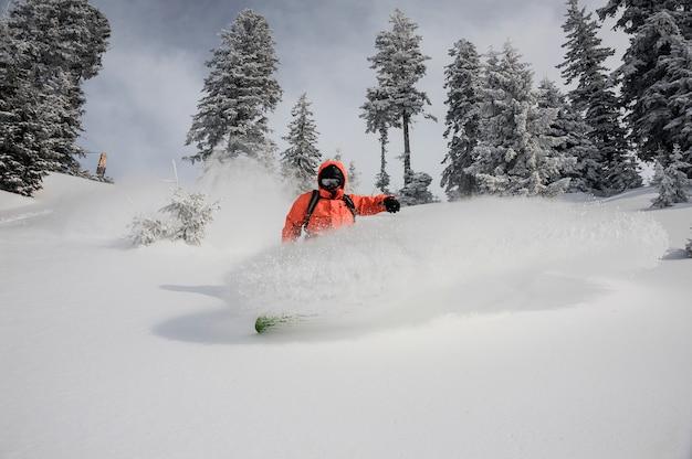 Jonge snowboarder die onderaan de mooie berg berijdt Premium Foto
