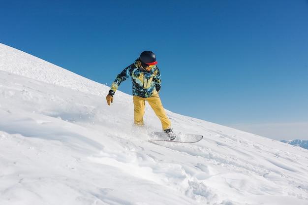 Jonge snowboarder in stijlvolle sportkleding rijden de helling af in georgië, gudauri Premium Foto