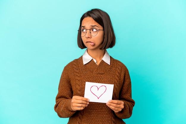 Jonge spaanse gemengd ras vrouw met een hart papier verward, voelt twijfelachtig en onzeker. Premium Foto