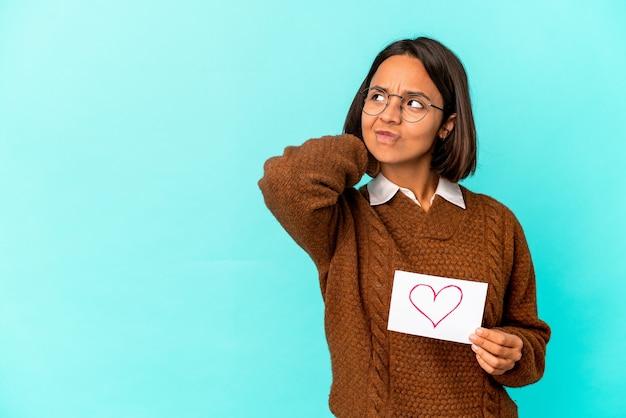 Jonge spaanse gemengde rasvrouw die een hartdocument houdt dat achterkant van het hoofd raakt, denkt en een keus maakt. Premium Foto