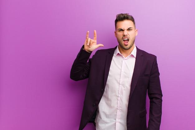 Jonge spaanse man voelt zich gelukkig, leuk, zelfverzekerd, positief en opstandig, waardoor rock of heavy metal met de hand tekent Premium Foto