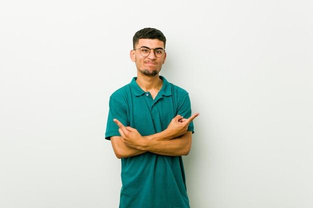 Jonge spaanse man wijst zijwaarts, probeert te kiezen tussen twee opties. Premium Foto