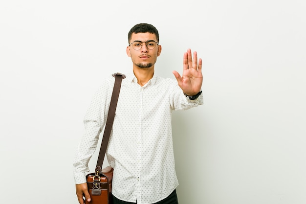 Jonge spaanse toevallige bedrijfsmens die zich met uitgestrekte hand bevinden die eindeteken tonen, die u verhinderen. Premium Foto