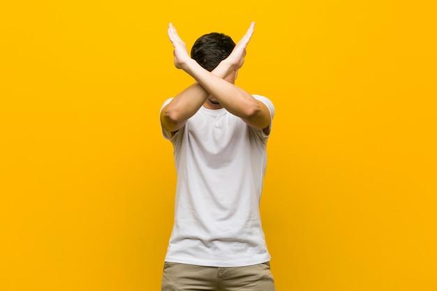 Jonge spaanse toevallige mens die twee wapens gekruist houden, ontkenningsconcept. Premium Foto