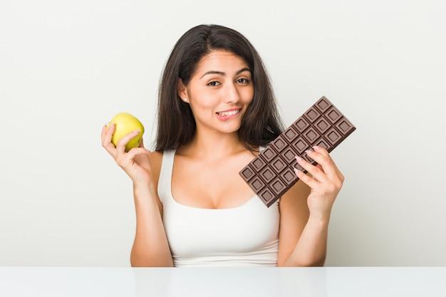 Jonge spaanse vrouw die tussen appel of chocoladetablet kiest Premium Foto