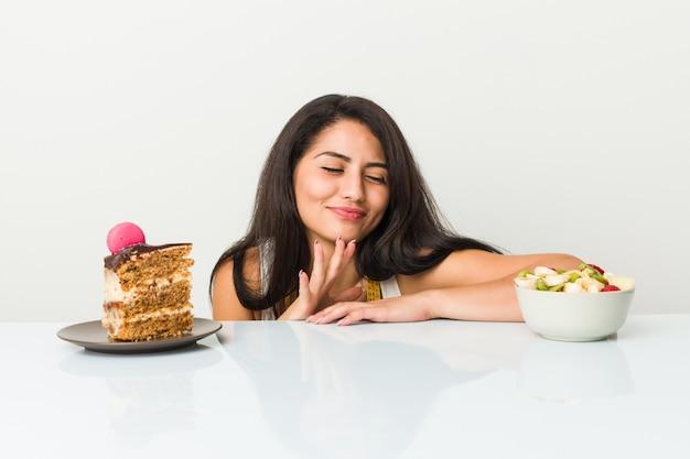 Jonge spaanse vrouw die tussen cake of fruitkom kiest Premium Foto