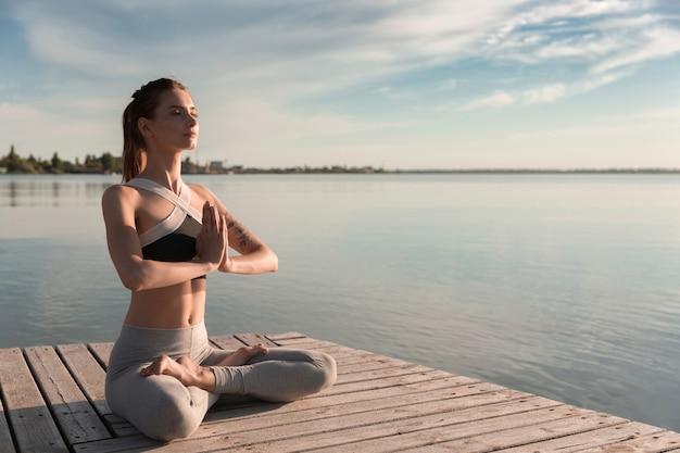 Jonge sport dame op het strand maken meditatie-oefeningen. Gratis Foto
