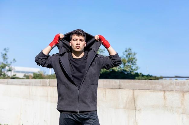 Jonge sport fitness man buiten in park maken boksoefeningen. Premium Foto