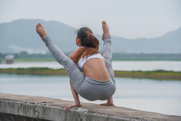 Jonge sportenvrouw die yoga op het meer met bergachtergrond doen. Premium Foto