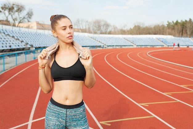 Jonge sportenvrouw na training met handdoek op zijn schouders op het stadion na het runnen van training Premium Foto