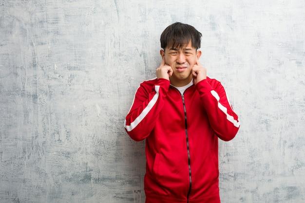 Jonge sportfitness chinees die oren behandelen met handen Premium Foto