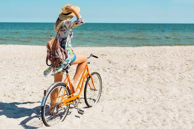 Jonge sportieve vrouw in stijlvolle witte crop top en denim shorts staande op het strand met oranje fiets Gratis Foto