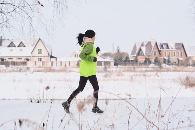 Jonge sportieve vrouw met paardenstaart die dicht bij plattelandshuizen loopt tijdens het trainen in de winter Premium Foto