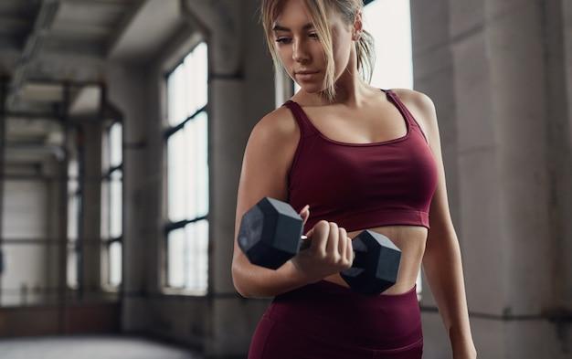 Jonge sportieve vrouw trainen met halter tijdens het trainen van biceps spieren tijdens fitnesstraining in de sportschool Premium Foto