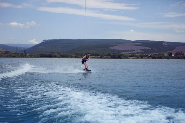 Jonge sportman die over meer surft. surfer in natte zwembroek traint in wake park, wakeboarden op de rivier, getrokken door motorboot, klampt zich vast aan kabel. wakesurfen, waterskiën, sport en recreatie Gratis Foto