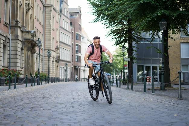Jonge sportman op een fiets in een europese stad. sporten in stedelijke omgevingen. Gratis Foto