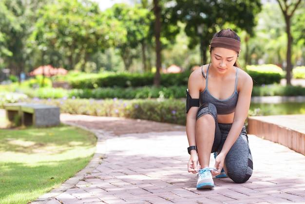 Jonge sportvrouw bindende schoenveter in park Gratis Foto