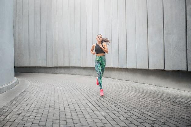 Jonge sportvrouw die in gang loopt Premium Foto