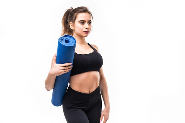 Jonge sportvrouw in zwarte sportkleding beoefenen van yoga op een mat. Gratis Foto