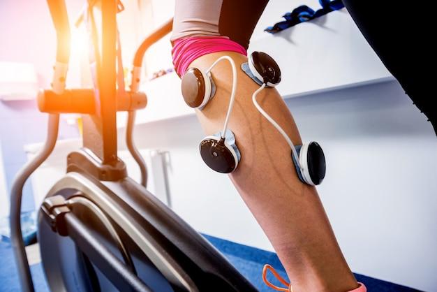 Jonge sportvrouw met elektrostimulator op de spieren van de benen. Premium Foto
