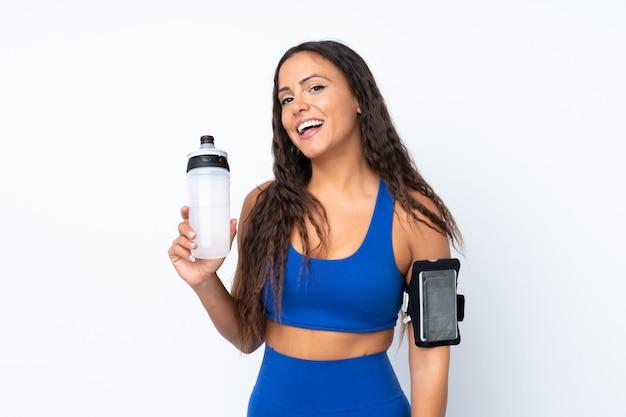 Jonge sportvrouw over geïsoleerd wit met de fles van het sportenwater Premium Foto