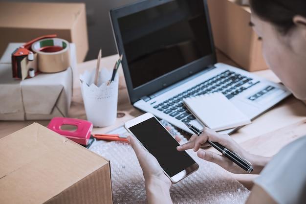 Jonge startup kleine bedrijfsondernemersvrouw die met slimme telefoon thuis werken Premium Foto