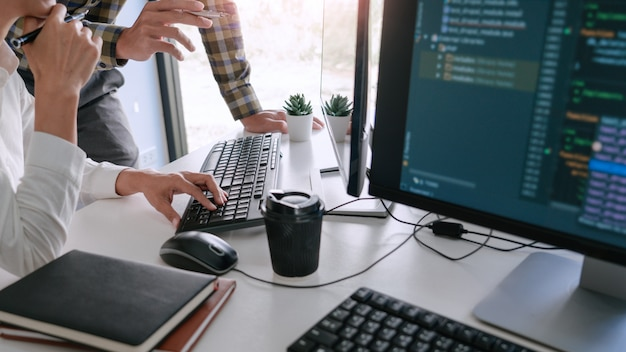 Jonge startup programmeurs zitten aan een bureau werken op computers scherm voor het ontwikkelen van programmeren en coderen om een oplossing voor het probleem met de nieuwe applicatie te vinden Premium Foto