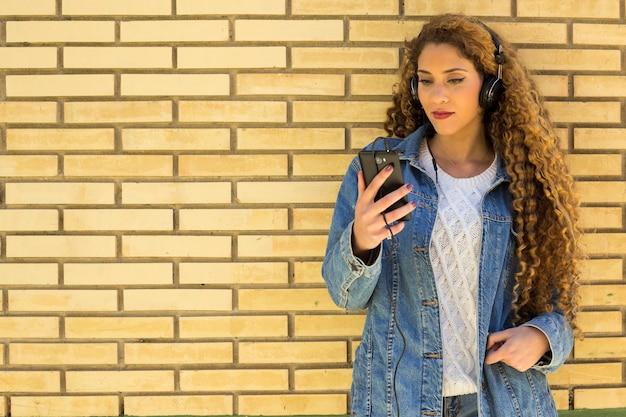 Jonge stedelijke vrouw met smartphone voor bakstenen muur Gratis Foto