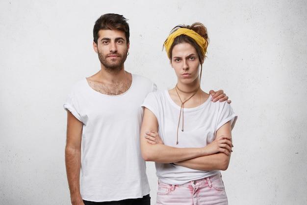 Jonge sterke man met baard en trendy kapsel omarmen zijn vriendin terwijl hij tegen een witte muur staat. Gratis Foto