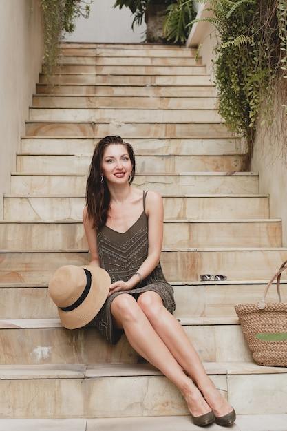 Jonge stijlvolle aantrekkelijke vrouw in elegante jurk zittend op trap, strooien hoed en tas, zomerstijl, modetrend, vakantie, glimlachen, stijlvolle accessoires, zonnebril, poseren op tropische villa op bali Gratis Foto