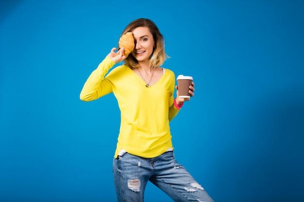 Jonge stijlvolle aantrekkelijke vrouw in gele blouse op blauw Gratis Foto