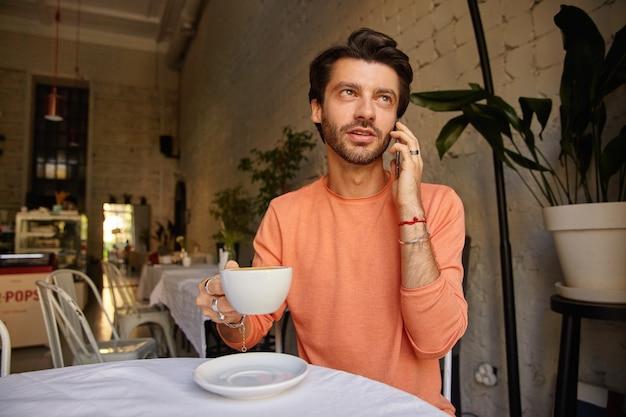 Jonge stijlvolle bebaarde man die zich voordeed op koffiehuis, praten aan de telefoon met kopje thee in de hand en praten over de telefoon, perzik kleur trui dragen Gratis Foto